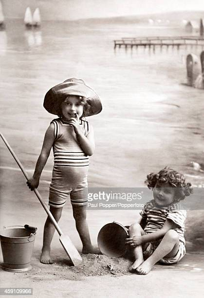 A studio photograph featuring two young children with buckets and spade playing with sand in front of a seaside backdrop circa 1913