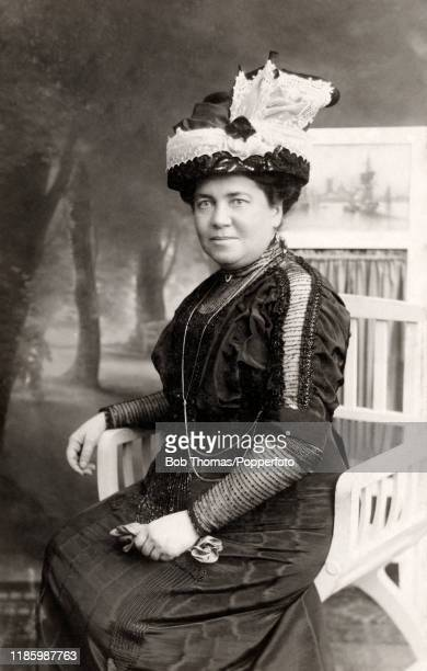 A studio portrait featuring a mature woman in her Sunday best clothes wearing an elaborate hat circa 1910