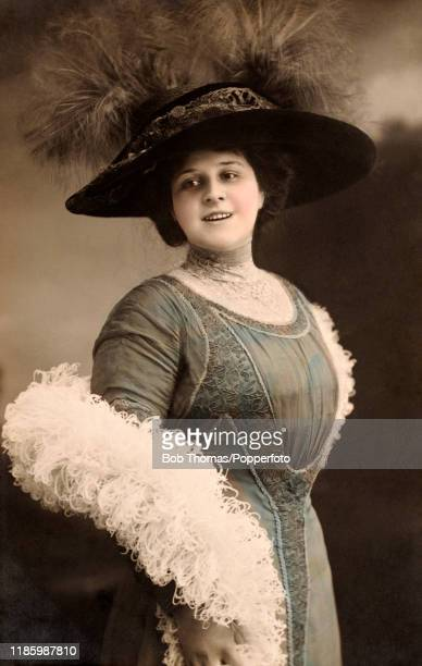 A studio portrait featuring a young woman wearing an elaborate feathered hat and a furry boa circa 1910