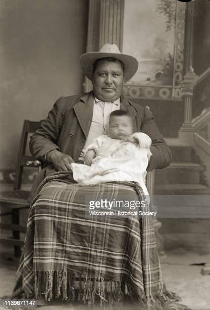 Studio portrait in front of a painted backdrop of a HoChunk man posing sitting and wearing a suit and hat and with a shawl on his lap Black River...