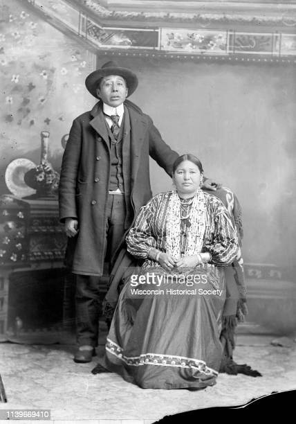 Studio portrait in front of a painted backdrop of a HoChunk man posing standing next to his wife who is posing sitting Black River Falls Wisconsin...