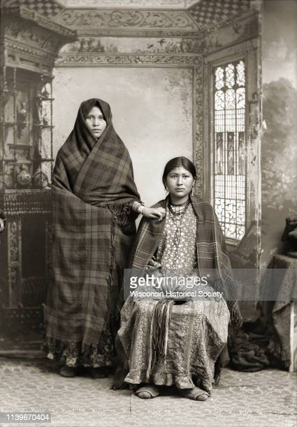 Studio portrait in front of a painted backdrop of a HoChunk woman posing standing on the left wearing rings and file bracelets and wrapped in a plaid...