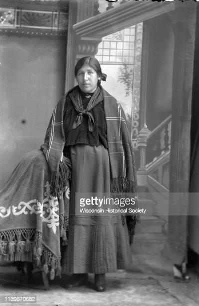 Studio portrait in front of a painted backdrop of a young HoChunk woman posing standing Black River Falls Wisconsin 1900 She is wearing a dark blouse...