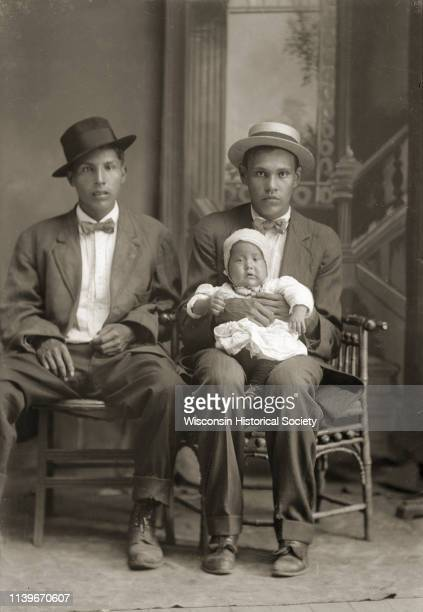 Studio portrait in front of a painted backdrop of two HoChunk men posing sitting and wearing suits bow ties and hats Black River Falls Wisconsin 1911...