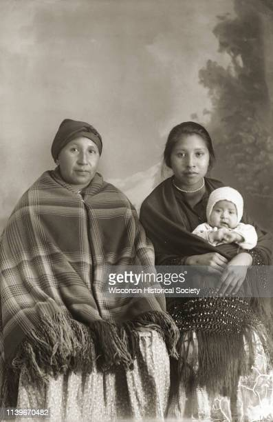 Studio portrait in front of a painted backdrop of two HoChunk women and and infant Black River Falls Wisconsin 1913 On the left is Mae Mary Smith...