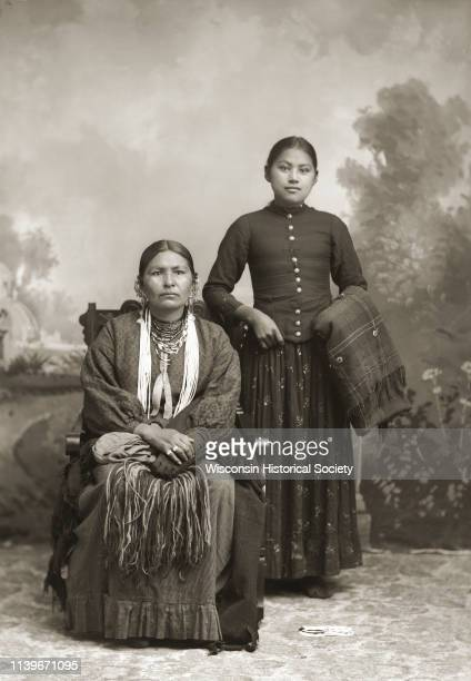 Studio portrait in front of a painted backdrop of two HoChunk women Black River Falls Wisconsin 1890 On the left a woman is posing sitting and is...