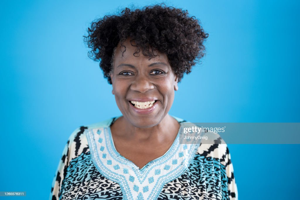 Studio portrait of 64 year old black woman smiling at camera : Stock Photo