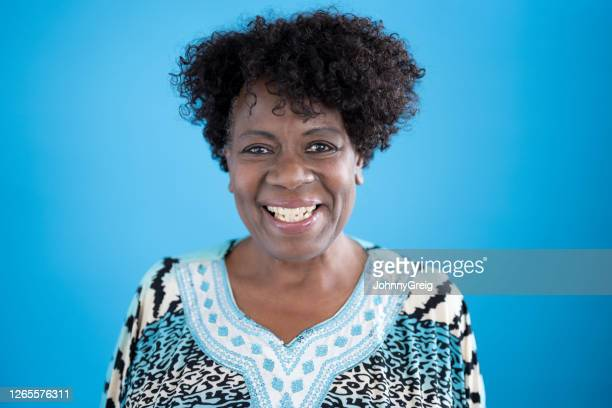 studio portrait of 64 year old black woman smiling at camera - human face stock pictures, royalty-free photos & images