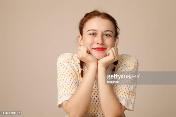 verticale de studio d'une femme rouge-cheveux attirante de 20 ans sur un fond beige - 18 19 ans photos et images de collection