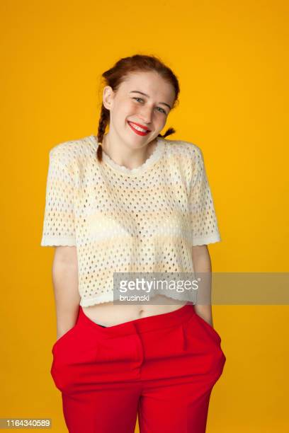 studio portrait of a 20 year old attractive red-haired woman on a yellow background - hands in pockets stock pictures, royalty-free photos & images
