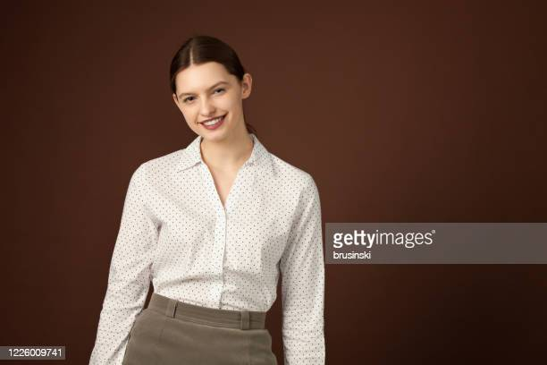 studio portrait of a 20 year old woman on brown background - blouse stock pictures, royalty-free photos & images