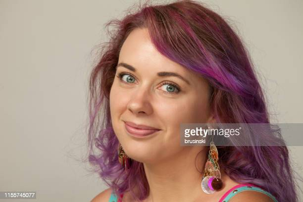 studio portrait of a 30 year old woman with purple hair on a gray background - purple hair stock pictures, royalty-free photos & images