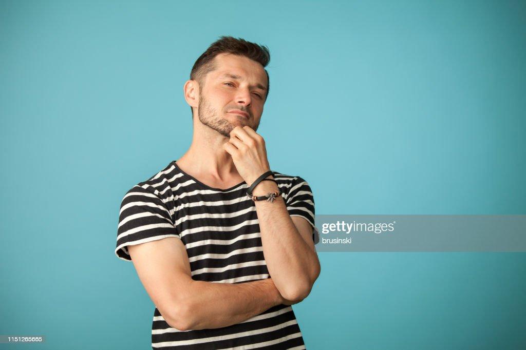 Portrait de Studio d'un homme barbu âgé de 40 ans dans un t-shirt rayé sur un fond bleu : Photo