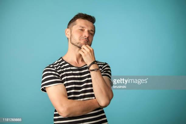 Portrait de Studio d'un homme barbu âgé de 40 ans dans un t-shirt rayé sur un fond bleu