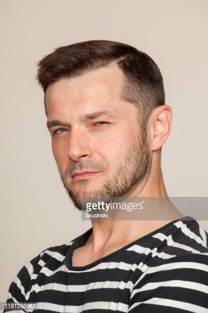 Portrait de Studio d'un homme barbu âgé de 40 ans dans un t-shirt rayé sur un fond beige
