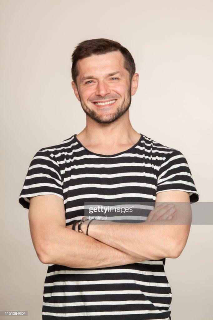 Portrait de Studio d'un homme barbu âgé de 40 ans dans un t-shirt rayé sur un fond beige : Photo