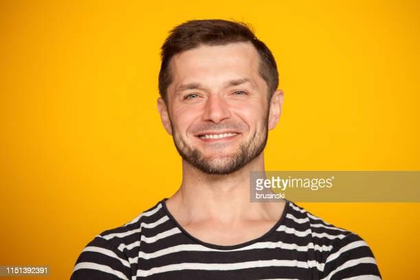 Portrait de Studio d'un homme barbu âgé de 40 ans dans un t-shirt rayé sur un fond jaune