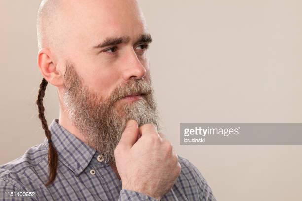 Portrait de Studio d'un homme barbu de 40 ans avec une tête rasée dans une chemise à carreaux sur un fond beige