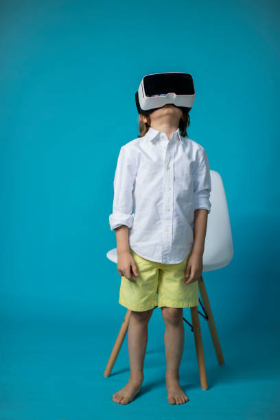 Studio portrait of a 5 year old boy wearing virtual reality glasses