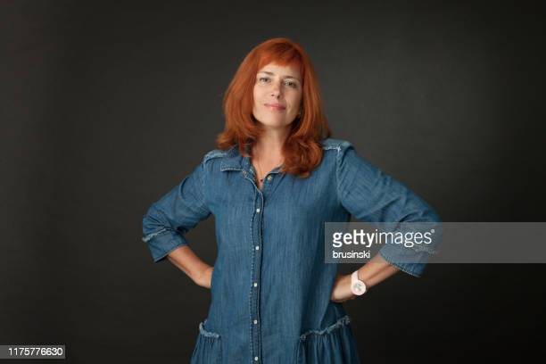studio portrait of a 50 year old attractive red-haired woman in a blue dress on a black background - one mature woman only stock pictures, royalty-free photos & images
