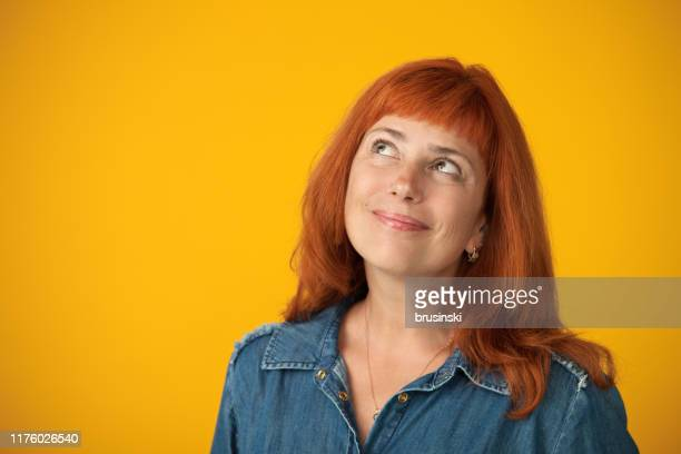 studio portrait of a 50 year old attractive red-haired woman in a blue dress on a yellow background - yellow background stock pictures, royalty-free photos & images