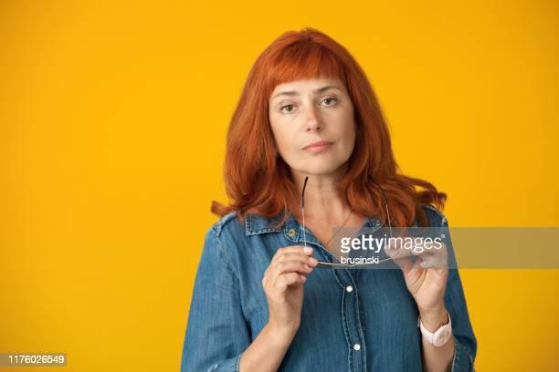 verticale de studio d'une femme rouge-cheveux attirante de 50 ans dans une robe bleue retenant des glaces dans ses mains sur un fond jaune - cadrage à la taille photos et images de collection