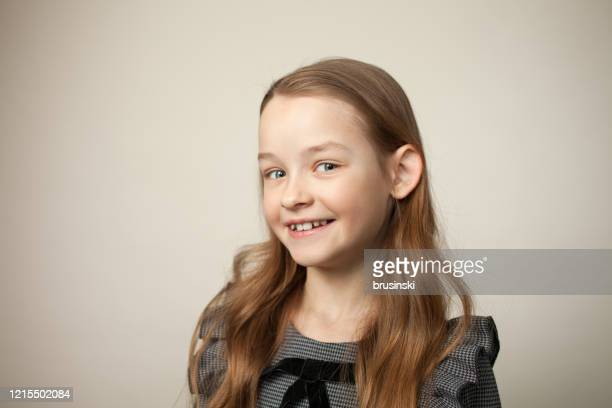 studioportret van een 9 éénjarigenmeisje op een beige achtergrond - 8 9 jaar stockfoto's en -beelden