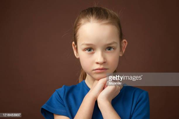 studio portrait of a 9 year old girl on a brown background - ponytail stock pictures, royalty-free photos & images