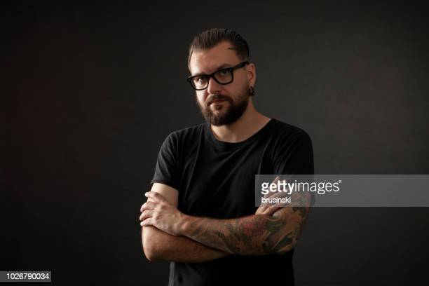 studio portrait of a bearded man wearing glasses on a black background - punk person stock pictures, royalty-free photos & images