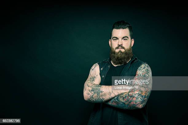studio portrait of a bearded man with tattooed arms - tattoo stock pictures, royalty-free photos & images