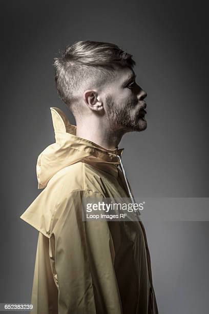 Studio portrait of a bearded young man in a yellow wind cheater
