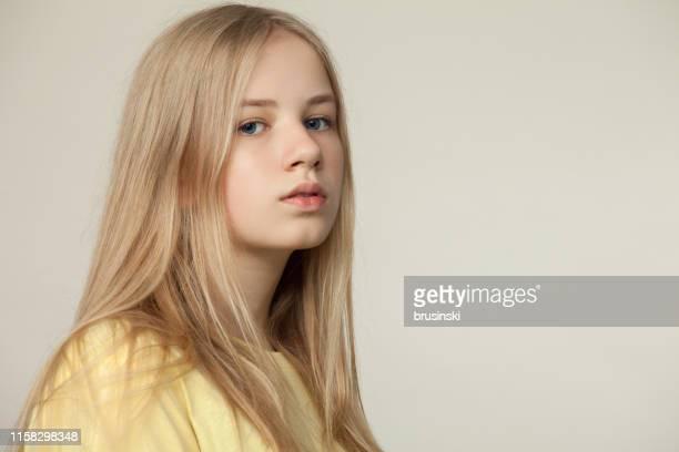 studio portret van een blonde tiener meisje in een geel t-shirt op een beige achtergrond - 14 15 jaar stockfoto's en -beelden