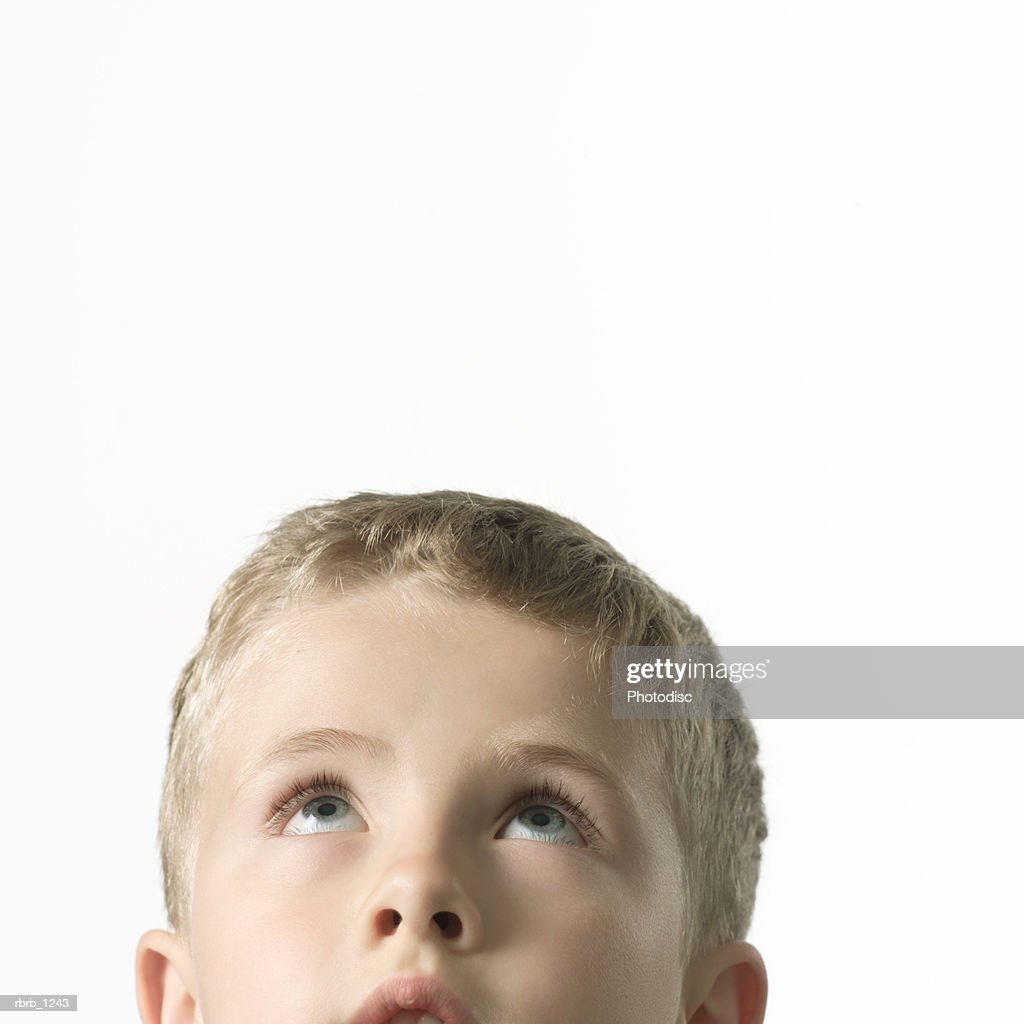 studio portrait of a caucasian blonde male childs as he glances up : ストックフォト