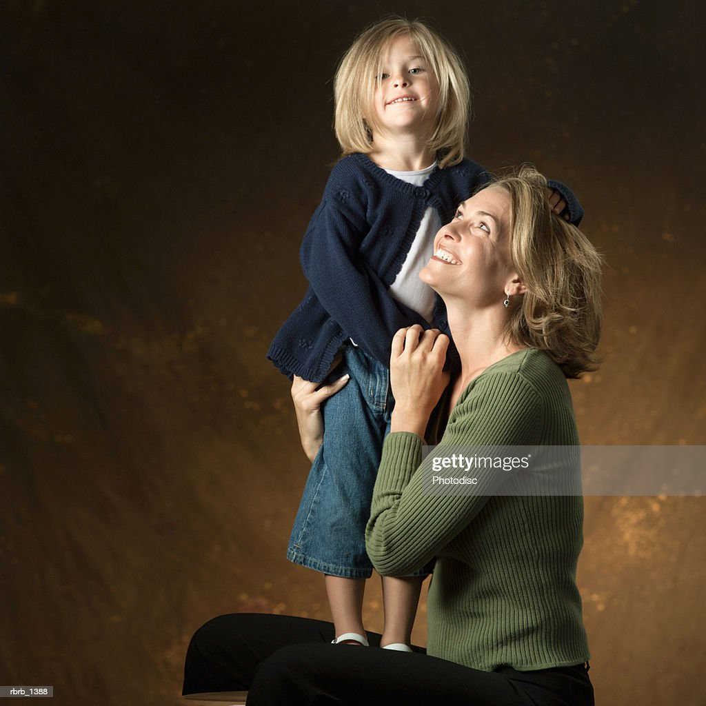 studio portrait of a caucasian blonde mother looking at her young blonde daughter standing on her lap : Stockfoto