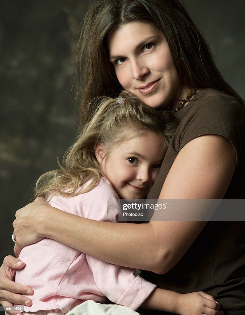 studio portrait of a caucasian brunette mother embracing her young blonde daughter : Stockfoto