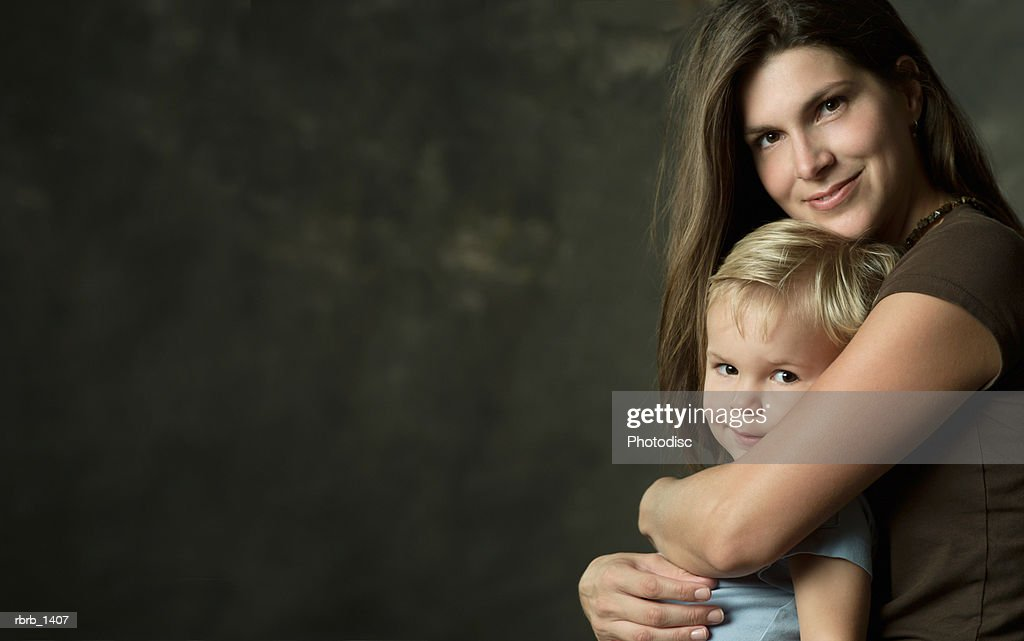 studio portrait of a caucasian brunette mother embracing her young blonde son : Stock Photo