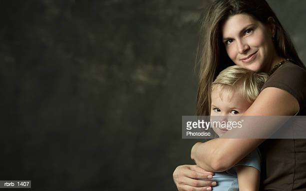 studio portrait of a caucasian brunette mother embracing her young blonde son