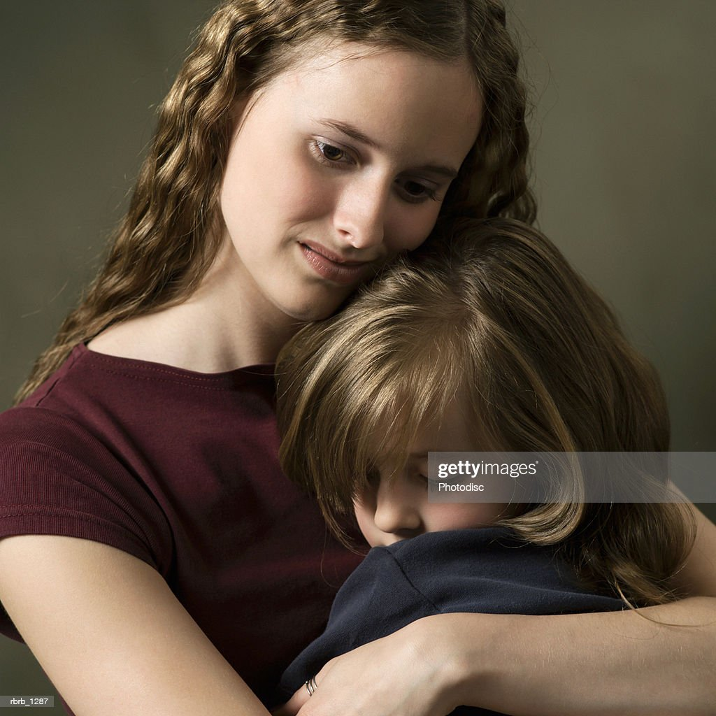 studio portrait of a caucasian female child with a purple shirt hugging her little sister tightly : Photo