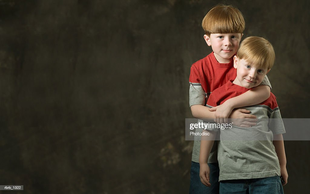 studio portrait of a caucasian redheaded male child as he puts his arms around his little brother as they smile : Stockfoto
