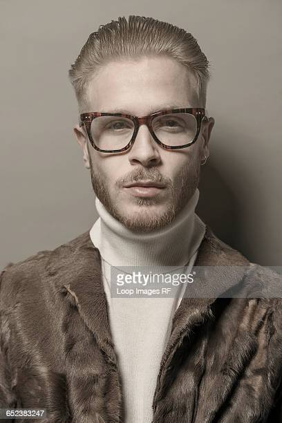 studio portrait of a cool young man with glasses wearing a fur jacket - オールバック ストックフォトと画像
