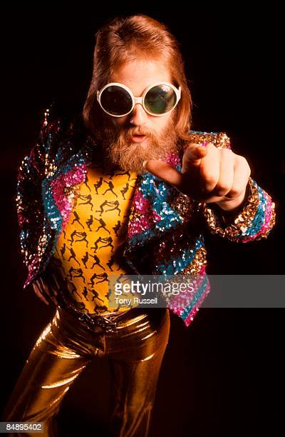 A studio portrait of a generic early 1970s glam rocker wearing sunglasses sparkling jacket and gold trousers circa 1972