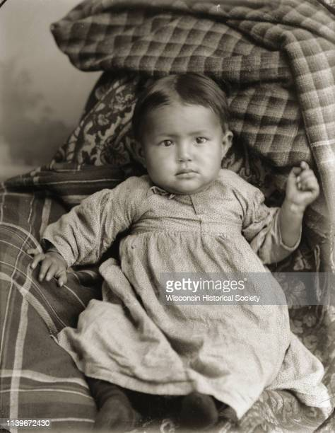 Studio portrait of a HoChunk infant John Stacy Jr posing sitting on a pile of fabrics and wearing a dress Black River Falls Wisconsin 1901 He is...