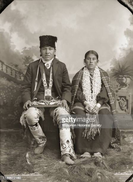 Studio portrait of a HoChunk man and woman posing sitting in front of a painted backdrop Black River Falls Wisconsin 1895 They are identified as Ed...