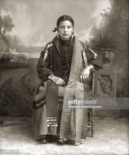Studio portrait of a HoChunk woman Alice Mary Blackdeer Hopkinah posing sitting in front of a painted backdrop Black River Falls Wisconsin 1908 She...