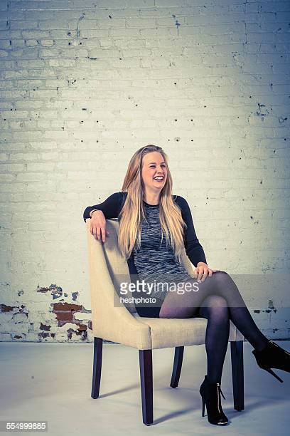 studio portrait of a laughing young woman sitting in a chair - heshphoto - fotografias e filmes do acervo