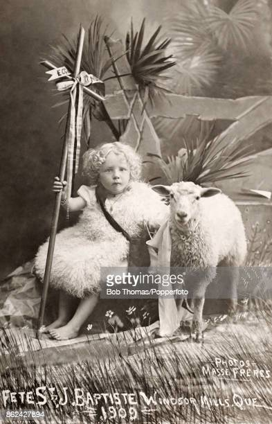 A studio portrait of a little girl dressed as a shepherdess with a staff and sheep during the Fete of St John Baptiste in Windsor Mills Quebec Canada...