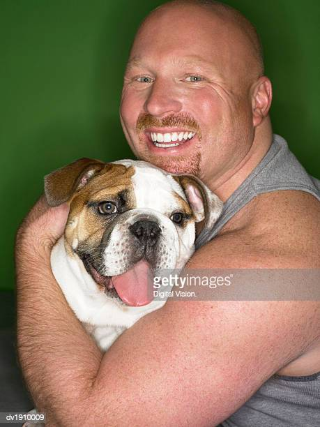 studio portrait of a man hugging his bulldog - alleen één mid volwassen man stockfoto's en -beelden