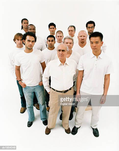 Studio Portrait of a Mixed Age, Multiethnic, Large Group of Displeased Men Wearing White Tops