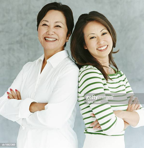 Studio Portrait of a Mother and Daughter Standing Back to Back, Smiling at the Camera