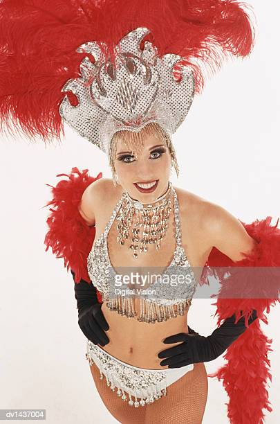 Studio Portrait of a Showgirl With a Sequined Headdress and Feather Boa Standing With Her Hands on Her Hips